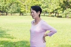 Азиатская старшая боль в спине женщины стоковая фотография