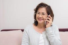 Азиатская старшая женщина жизнерадостно беседуя с друзьями на передвижном пэ-аш стоковые фотографии rf