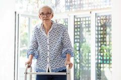Азиатская старшая женщина используя ходока во время реабилитации, пожилая женщина с идти и работать дома стоковые фотографии rf
