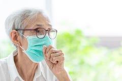 Азиатская старшая женщина пострадать от кашля с предохранением от лицевого щитка гермошлема, лицевым щитком гермошлема пожилой же стоковое изображение