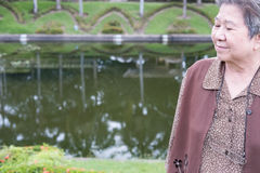 Азиатская старшая женщина стоя в саде пожилые старшие женские остатки Стоковая Фотография RF