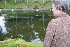 Азиатская старшая женщина стоя в саде пожилые старшие женские остатки Стоковые Фотографии RF