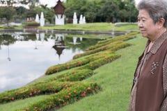Азиатская старшая женщина стоя в саде пожилые старшие женские остатки Стоковая Фотография