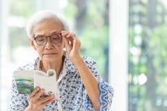 Азиатская старшая женщина читая книгу ослабленную дома, пожилая женщина тратит их книгу чтения свободного времени стоковое фото
