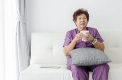 Азиатская старшая питьевая вода женщины, сидя на кресле около окна Стоковая Фотография RF