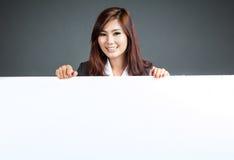 Азиатская стойка коммерсантки за пустыми знаменем и улыбкой Стоковое фото RF