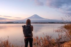 Азиатская стойка молодого человека смотря Mount Fuji на озере Kawaguchiko на стоковое фото rf