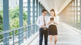 Азиатские бизнесмены идя и говоря вне офиса Стоковые Изображения