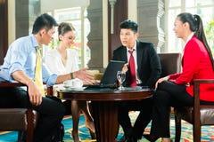 Азиатские бизнесмены на встрече в лобби гостиницы Стоковое Изображение