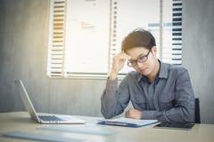 Азиатские бизнесмены серьезные о работе сделанной до головной боли стоковые изображения