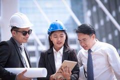 Азиатские бизнесмен и женщина обсуждают с prof архитектора инженера Стоковое фото RF