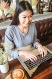 Азиатские бизнес-леди используя компьтер-книжку в кофейне стоковое фото