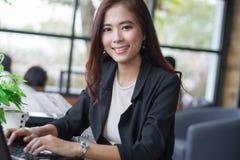 Азиатские бизнес-леди используя тетрадь и бизнес-леди усмехаясь h Стоковые Фотографии RF