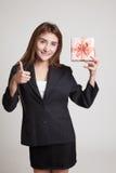 Азиатские большие пальцы руки женщины вверх с подарочной коробкой Стоковые Изображения