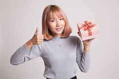 Азиатские большие пальцы руки женщины вверх с подарочной коробкой Стоковое Изображение RF