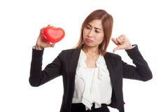 Азиатские большие пальцы руки бизнес-леди вниз с красным сердцем Стоковое Изображение RF