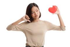 Азиатские большие пальцы руки бизнес-леди вниз с красным сердцем Стоковое фото RF