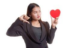 Азиатские большие пальцы руки бизнес-леди вниз с красным сердцем Стоковая Фотография