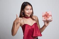 Азиатские большие пальцы руки женщины вверх с подарочной коробкой Стоковое Изображение