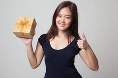 Азиатские большие пальцы руки женщины вверх с подарочной коробкой Стоковые Фото