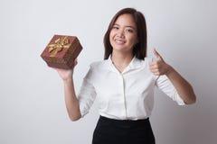 Азиатские большие пальцы руки женщины вверх с подарочной коробкой Стоковая Фотография RF