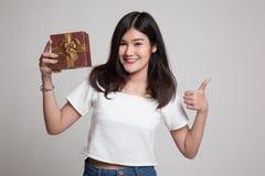 Азиатские большие пальцы руки женщины вверх с подарочной коробкой Стоковое Фото