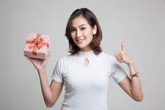 Азиатские большие пальцы руки женщины вверх с подарочной коробкой Стоковые Изображения RF