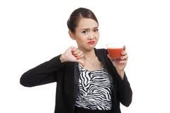 Азиатские большие пальцы руки женщины вниз ненавидят сок томата Стоковое Фото