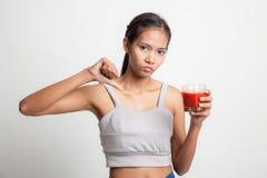 Азиатские большие пальцы руки женщины вниз ненавидят сок томата Стоковая Фотография