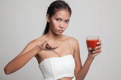 Азиатские большие пальцы руки женщины вниз ненавидят сок томата Стоковые Изображения RF