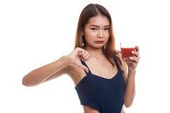Азиатские большие пальцы руки женщины вниз ненавидят сок томата Стоковое Изображение