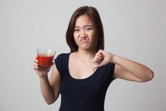 Азиатские большие пальцы руки женщины вниз ненавидят сок томата Стоковое фото RF