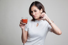 Азиатские большие пальцы руки женщины вниз ненавидят сок томата Стоковые Фотографии RF
