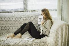 Азиатские девушки вручают книгу удерживания и усмехаться счастливо на кресле в доме с релаксацией, концепцией устанавливать цели  стоковое фото rf