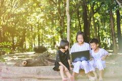 Азиатские девушки и мальчик используя тетрадь искать некоторую информацию Стоковая Фотография RF