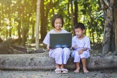 Азиатские девушки и мальчик используя тетрадь искать некоторую информацию Стоковые Изображения RF