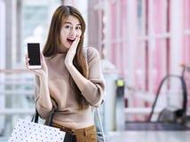 Азиатские девушки с хозяйственными сумками используя smartphone Стоковое Фото