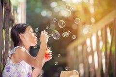 Азиатские девушки играют дуя пузыри на мосте Стоковое фото RF