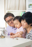 Азиатские деньги сбережений семьи крытые Стоковые Изображения