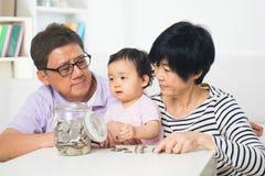 Азиатские деньги сбережений семьи крытые Стоковые Изображения RF