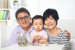 Азиатские деньги сбережений семьи крытые Стоковое фото RF