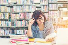 Азиатские женщины в чтении и думать библиотеки что-то в книге в библиотеке стоковое фото rf