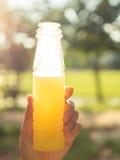 Азиатские женщины держа бутылку апельсинового сока Стоковая Фотография