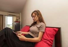 Азиатские женщины используют таблетку на кровати в утре Азиатская женщина в кровати проверяя социальные apps Стоковые Фото