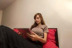 Азиатские женщины используют таблетку на кровати в утре Азиатская женщина в кровати проверяя социальные apps Стоковая Фотография RF