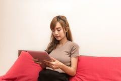 Азиатские женщины используют таблетку на кровати в утре Азиатская женщина в кровати проверяя социальные apps Стоковое Изображение RF