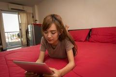 Азиатские женщины используют таблетку на кровати в утре Азиатская женщина в кровати проверяя социальные apps Стоковые Фотографии RF