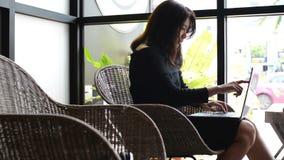 Азиатские женщины используя ноутбук для работы на кофейне сток-видео