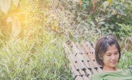 Азиатские женщины кладя на качание кладут в постель в саде Стоковые Фото