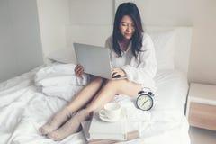 Азиатские женщины на белой кровати Бодрствование чтения женщин вверх и работающ на книге ноутбука и чтения и выпивая кофе в утре  стоковое фото rf